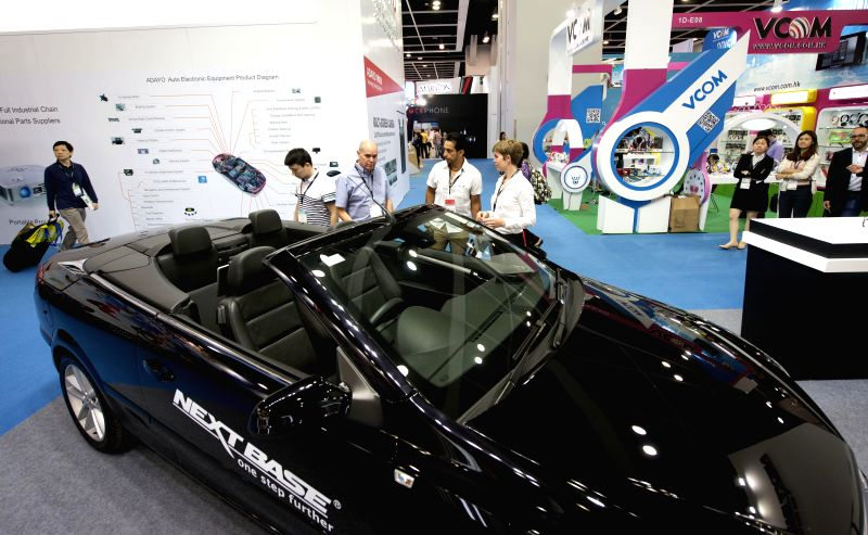 Visitors look at a new type of electric car at the Hong Kong Electronics Fair (Spring Edition) in south China's Hong Kong, April 13, 2015. The four-day fair, ...