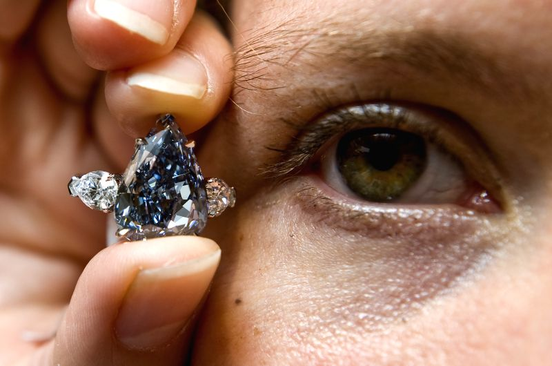 A Christie's employee shows a blue diamond, weighing 13.22 carats, at Christie's in Hong Kong, south China, April 24, 2014. The diamond, estimated to fetch at 21