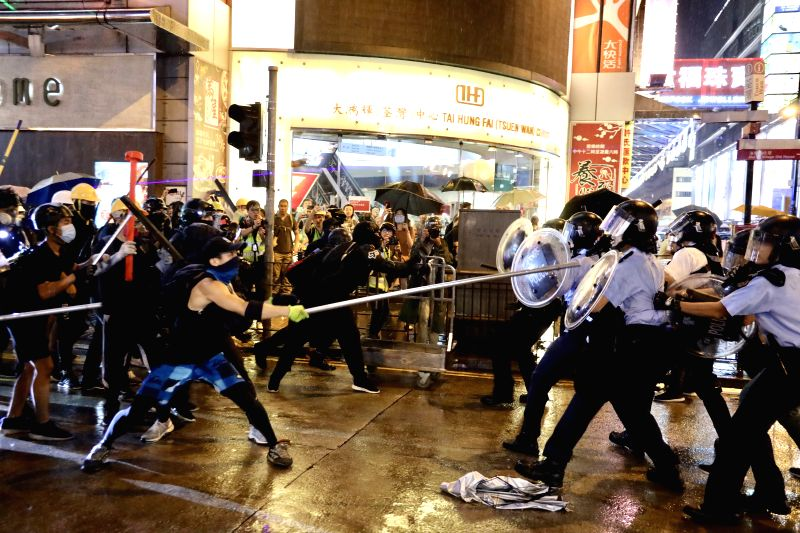 HONG KONG, Aug. 25, 2019 (Xinhua) -- Radical protesters attack police officers in Tsuen Wan, in the western New Territories of south China's Hong Kong, Aug. 25, 2019. Radical protesters block various roads, hurl bricks and stones at police officers i