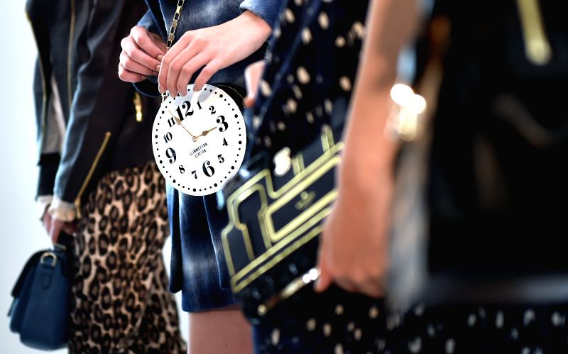 Models show handbags at the preview of the autumn fashion collection of Kate Spade in Hong Kong, south China, July 3, 2014.