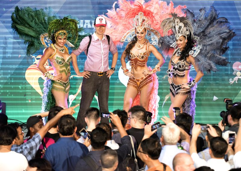 HONG KONG, June 13, 2017 - A tourist poses for photos with dancers in Hong Kong, south China, June 7, 2017. Hong Kong is crowned as the fashion capital of Asia and has a significant influence on the ...