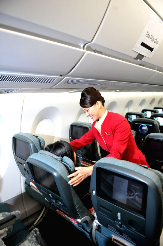 HONG KONG, May 31, 2016 - A flight attendant instructs a visitor to operate the seat at A350 XWB aircraft in Hong Kong, south China, May 30, 2016.  Cathay Pacific Airways received its first A350 XWB ...