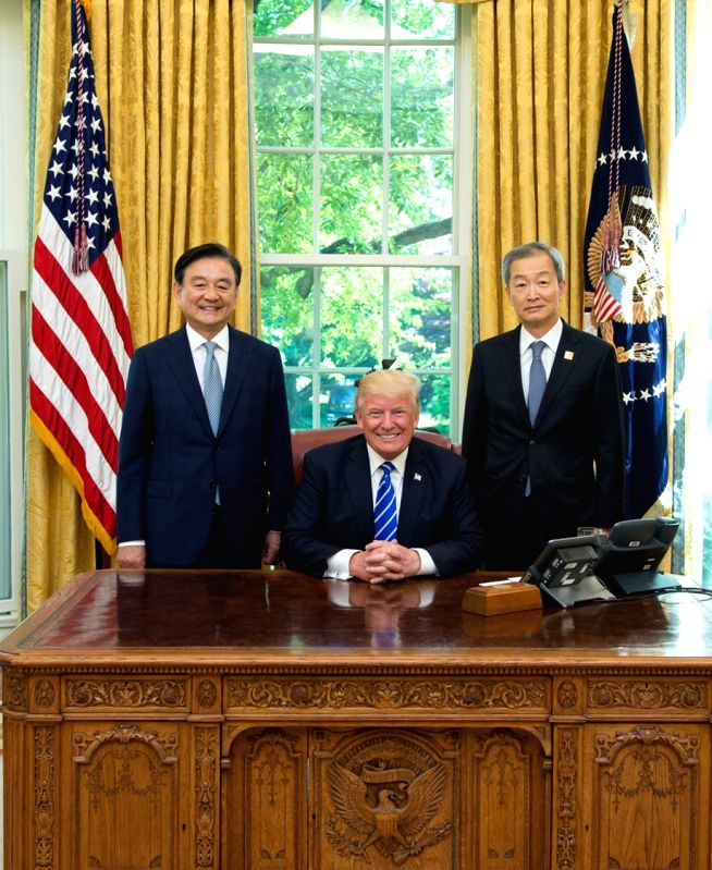 Hong Seok-hyun (L), a special envoy of South Korean President Moon Jae-in, poses for a photo with U.S. President Donald Trump (C) during their meeting in the Oval Office at the White House in ...
