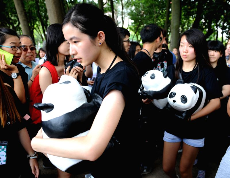 Staff members carry paper pandas to an exhibition at the Victoria Park, south China's Hong Kong, June 19, 2014. A total of 1,600 paper pandas were displayed here .. - Paulo Grangeon