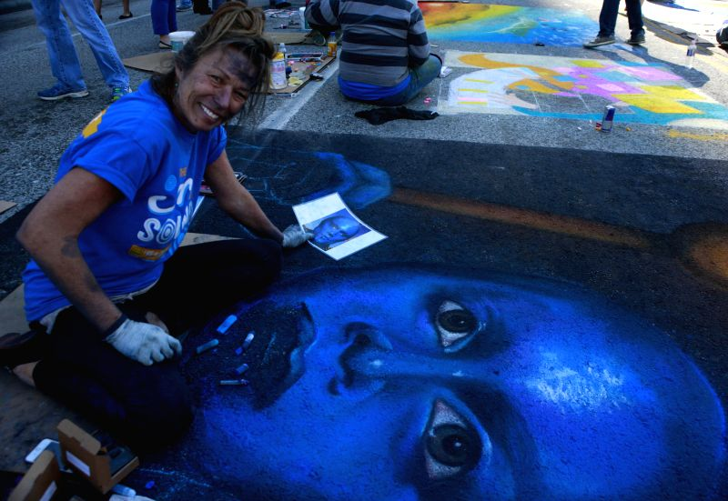 An artist paints during the street graffiti contest in Houston, the United States, on Nov. 23, 2014. Hundreds of paintings were created during the street graffiti contest in Houston. ...