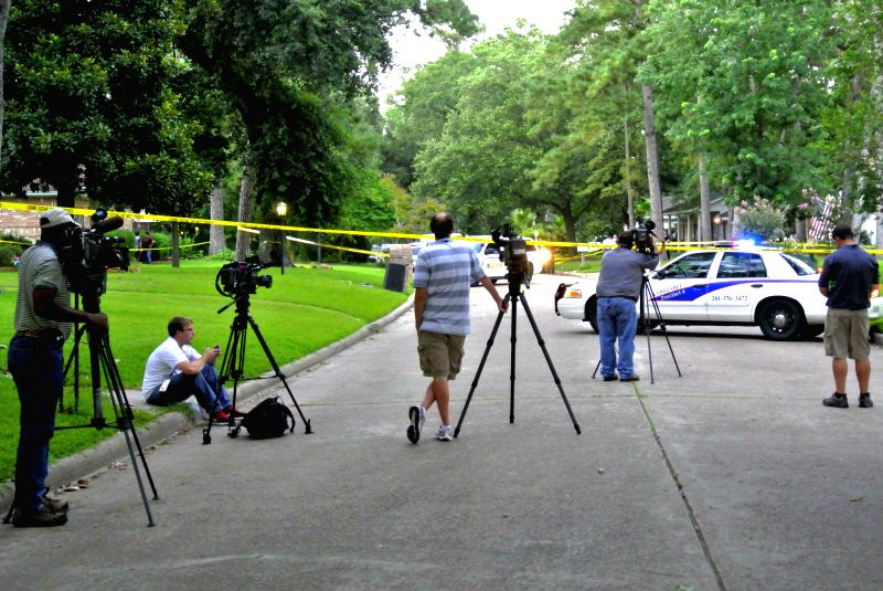 Journalists work near the shooting area in Houston, the United States, July 9, 2014. A man involved in a domestic dispute opened fire at a suburban Houston home ...