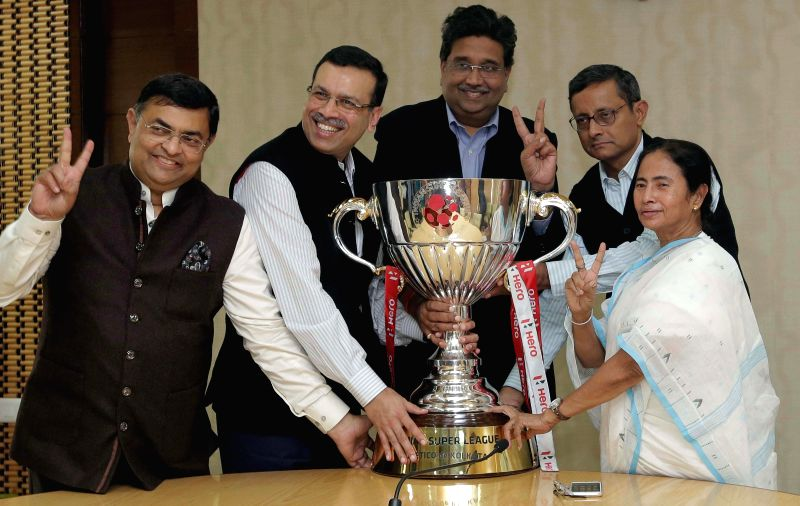 West Bengal Chief Minister Mamata Banerjee, Atletico de Kolkata team co-owner Sanjiv Goenka, and businessman Harshavardan Neotia with the ISL trophy at Nabanno - West Bengal secretariat - in . - Mamata Banerjee and Sanjiv Goenka