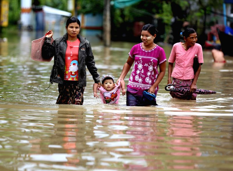HPA-Residents wade through flood water in Hpa-an, the capital of Kayin State, Myanmar, July 24, 2018. People in Kayin state are being affected by flood due to the ...