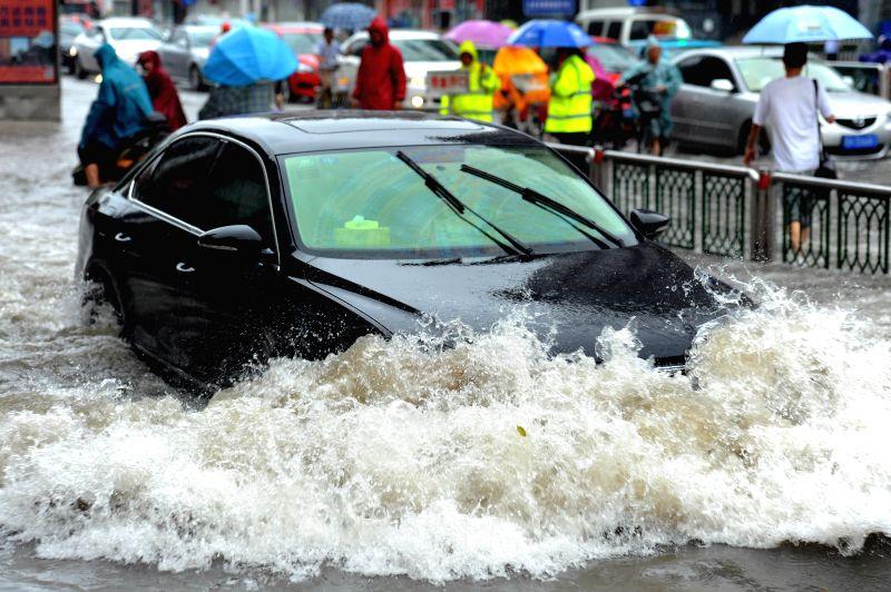 HUAI'A car makes its way along a waterlogged road in Huai'an, east China's Jiangsu Province, July 25, 2014. Typhoon Matmo, the 10th typhoon that affects China this year,