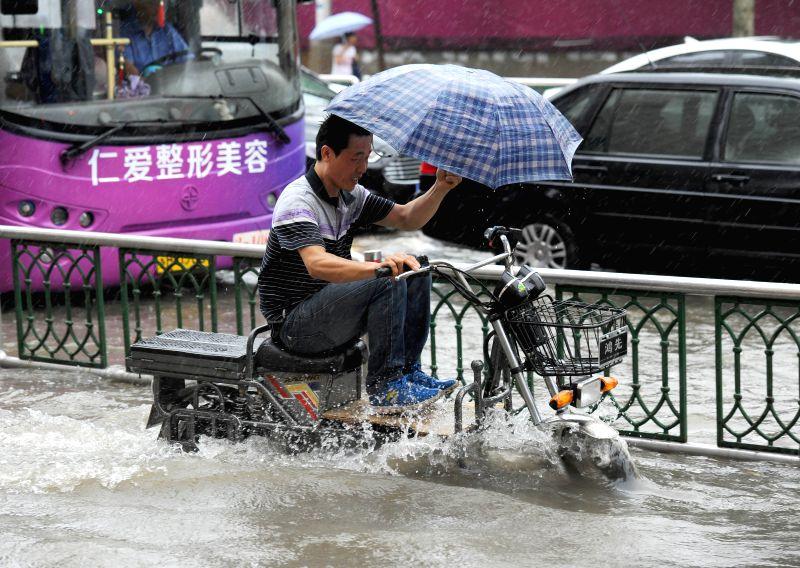 HUAI'A man rides an electronic scooter along a waterlogged road in Huai'an, east China's Jiangsu Province, July 25, 2014. Typhoon Matmo, the 10th typhoon that affects ...