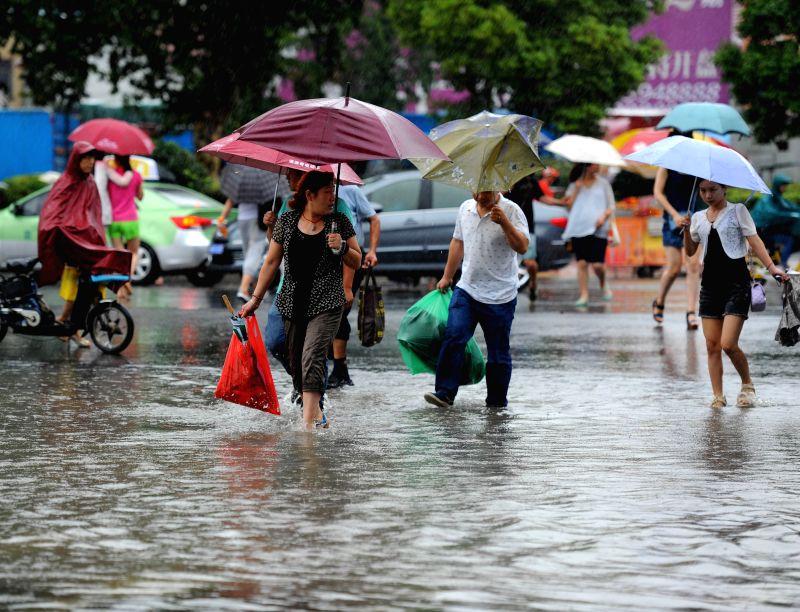 HUAI'Pedestrians wade along a waterlogged road in Huai'an, east China's Jiangsu Province, July 25, 2014. Typhoon Matmo, the 10th typhoon that affects China this year, ...