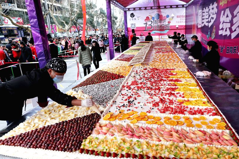 Bakers make a 24-square-meter cake at Huaihai Road in Huaibei City, east China's Anhui Province, Jan. 18, 2015. The cake took 9 bakers eight hours to finish it. ...