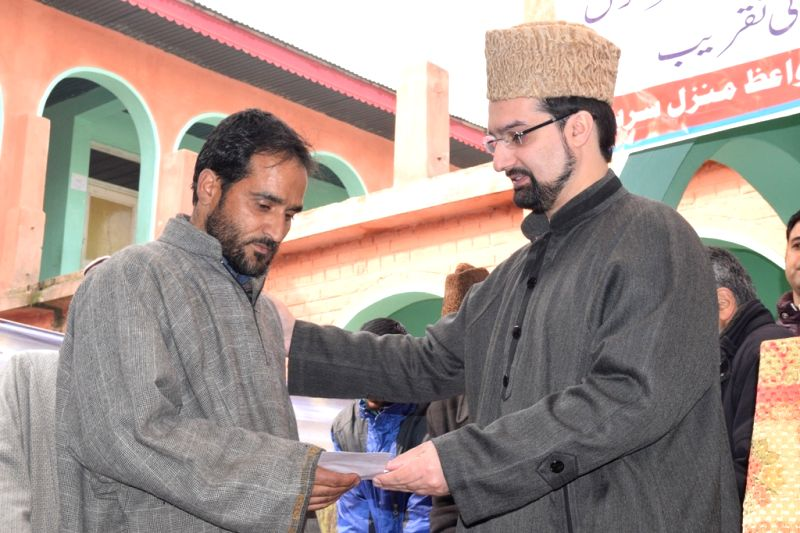 Hurriyat Conference (M) Chairman Mirwaiz Umar Farooq distributes compensation cheques to the victims of  2014 floods in Anantnag of Jammu and Kashmir on Dec 6, 2015.