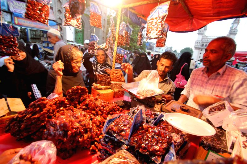 A woman busy buying dates on the first friday of Ramadan at Charminar in Hyderabad on June 19, 2015.