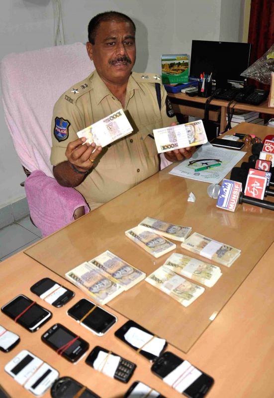 DCP B. Limba Reddy presents before press outdated Brazillian currency with a face value of two crore seven lakh rupees and 12 mobile phones  that was recovered by the police, during a ... - B. Limba Reddy