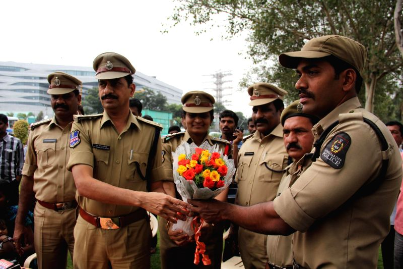 Deputy Commissioner of Police (Central Zone) V B Kamalasan Reddy greets the  home guard who prevented two children and their mother from committing suicide in Hyderabad, on Dec 11, 2014.