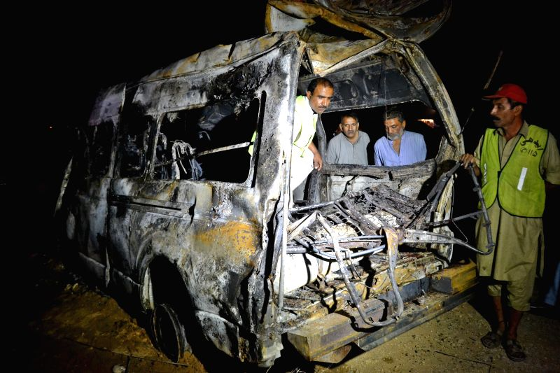 Rescuers examine the wreckage of a burnt passenger van at the accident site near southern Pakistan's Hyderabad, Feb. 23, 2015. At least 12 people were killed and ...