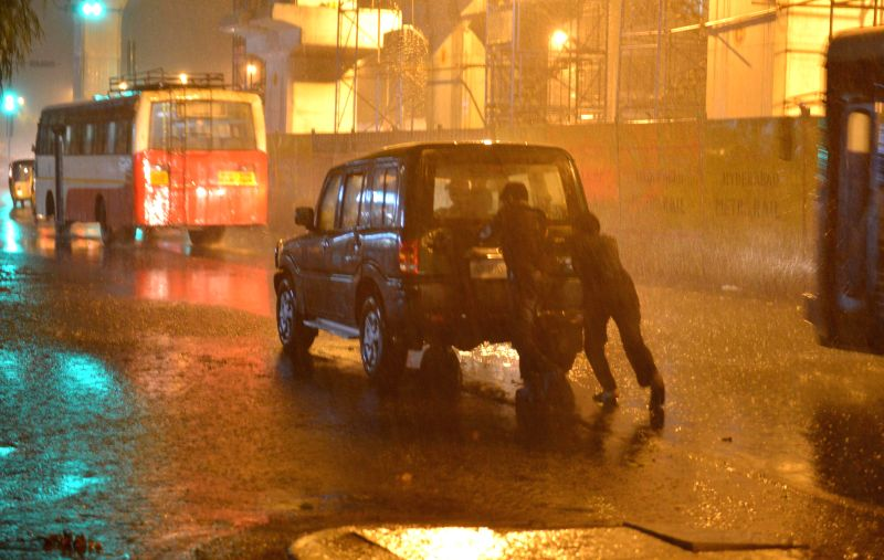 People push their car during rains in Hyderabad on Nov 12, 2014.