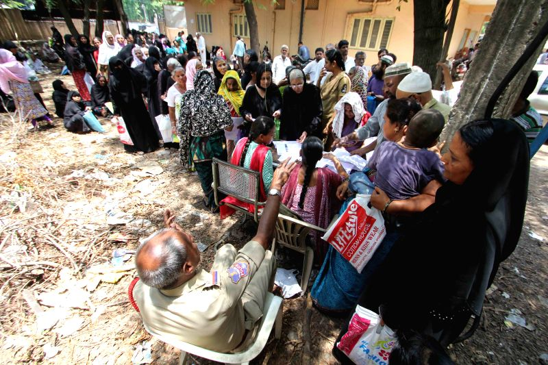 People queue-up outside a pension disbursal centre to collect the pension provided to them by the Telangana government under Aasara scheme in Hyderabad, on April 21, 2015.