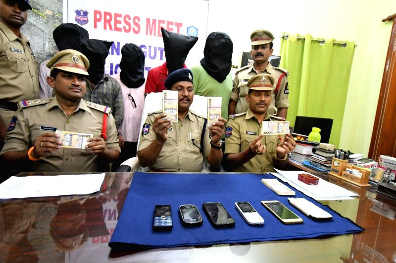 Hyderabad police personnel presents before press Brazillian currency and mobile phones that was recovered by the police, during a press conference in Hyderabad on July 21, 2016.