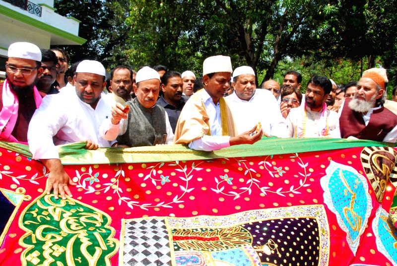 Telangana Chief Minister K Chandrasekhar Rao hands over the `Chaadar` to be offered at Dargah of Khwaja Moinuddin Chishti, Ajmer Sharif to a delegation in Hyderabad on April 21, 2015. - K Chandrasekhar Rao