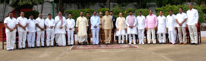 Telangana Governor E.S.L. Narasimhan Rao and Chief Minister K Chandrasekhar Rao with the newly appointed ministers in Hyderabad, on Dec 16, 2014. - K Chandrasekhar Rao and L. Narasimhan Rao