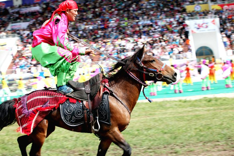 An equestrian stages a horse show during the opening ceremony of the 2014 China (Ili) Tianma International Tourism Festival in Zhaosu County of Ili, northwest China's ..