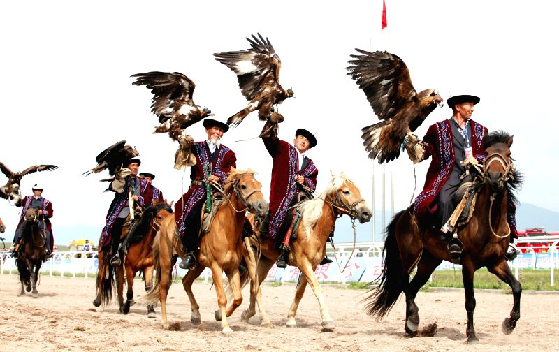 Equestrians stage an on-harness falcon show during the opening ceremony of the 2014 China (Ili) Tianma International Tourism Festival in Zhaosu County of Ili, northwest