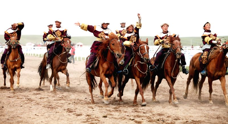 Young equestrians take part in a horse race during the opening ceremony of the 2014 China (Ili) Tianma International Tourism Festival in Zhaosu County of Ili, northwest