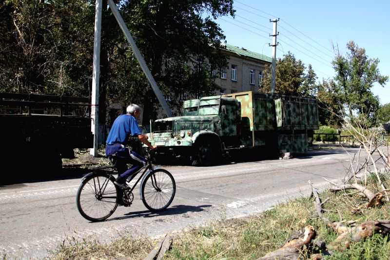 A local resident rides a bike past an abandoned military vehicle in Ilovaisk, Ukraine, on Sept 3, 2014. At least 87 Ukrainian soldiers were killed after being ...