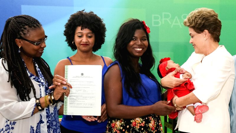 Image provided by Brasil's Presidency shows Brazilian President Dilma Rousseff (1st R) holding a girl during a ceremony for the Black Awareness Day, in Brasilia, ...