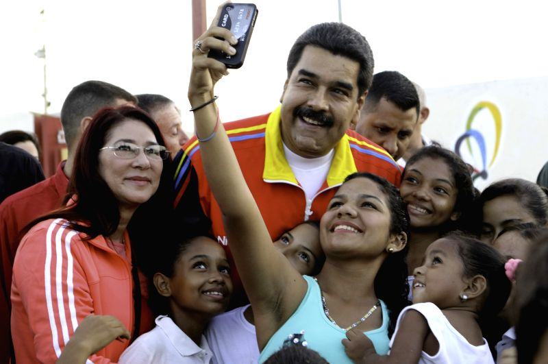 Image provided by Venezuela's Presidency, of Venezuelan President, Nicolas Maduro (C), and his wife Cilia Flores (L), the delivering ceremony of house number 800,000 ...