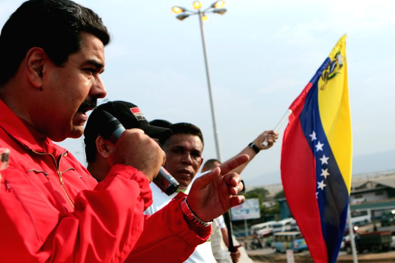 Image provided by Venezuela's Presidency shows Venezuelan President Nicolas Maduro (L), delivering a speech during the opening of the traffic solution number 35 ...