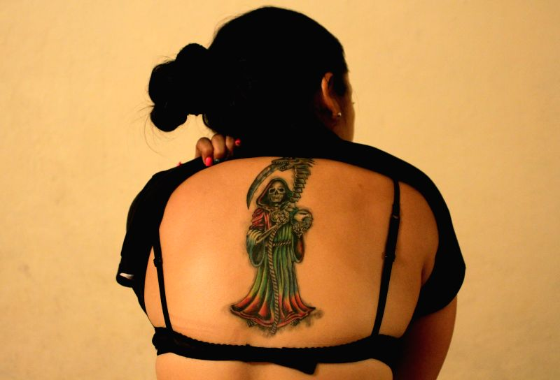 Image taken on Sept. 25, 2015, shows Jenni, who tattooed the image of the Holy Death, in Veracruz, Mexico. The cult to the Holy Death is a social phenomenon also ...
