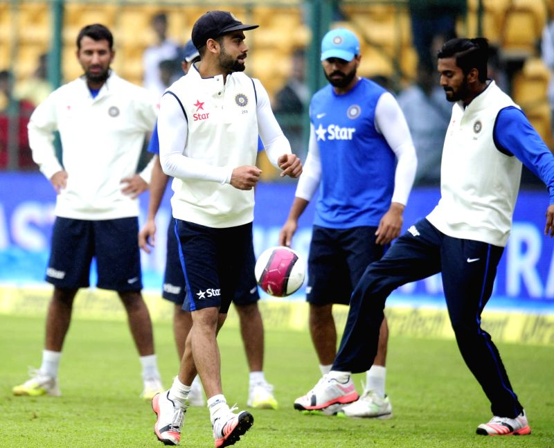 India cricketers Murali Vijay, Virat Kohli and Cheteswara Pujara warm up on the ground as rain delay the start of the 4th day of the second test match between India and South Africa at M ... - Virat Kohli