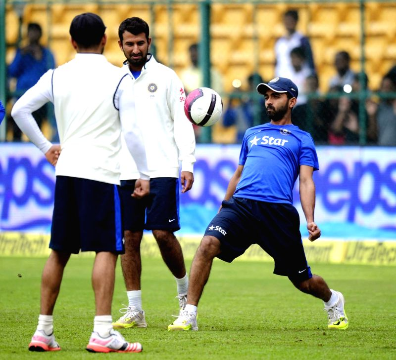 India cricketers Virat Kohli, Ajinkey Rahane and Cheteswara Pujara warm up on the ground as rain delay the start of the 4th day of the second test match between India and South Africa at M ... - Virat Kohli