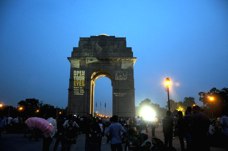 India Gate visitors look at a child rights message projected on the monument during a CRY campaign in New Delhi on July 27, 2014.