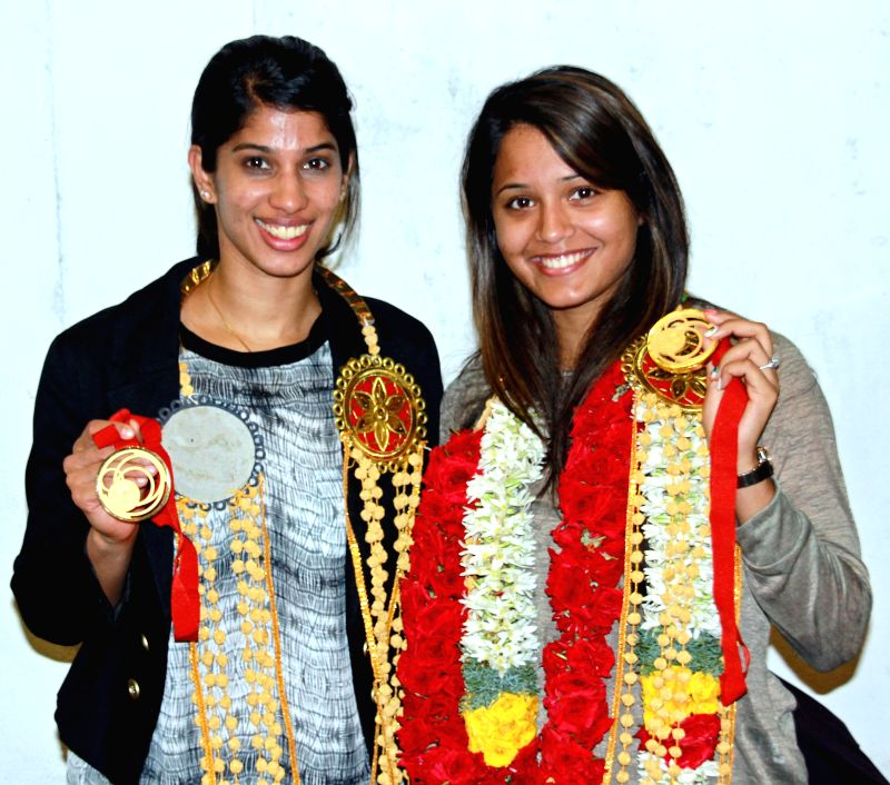 India's gold winning squash players Dipika Pallikal and Joshna Chinappa who won gold in Commonwealth Games, Glasgow 2014 pose for a photograph at Chennai Airport on Aug 5, 2014.