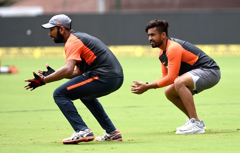 India's Karun Nair and Cheteshwar Pujara during a practice session ahead of their maiden cricket test match against Afghanistan in Bengaluru on June 13, 2018.
