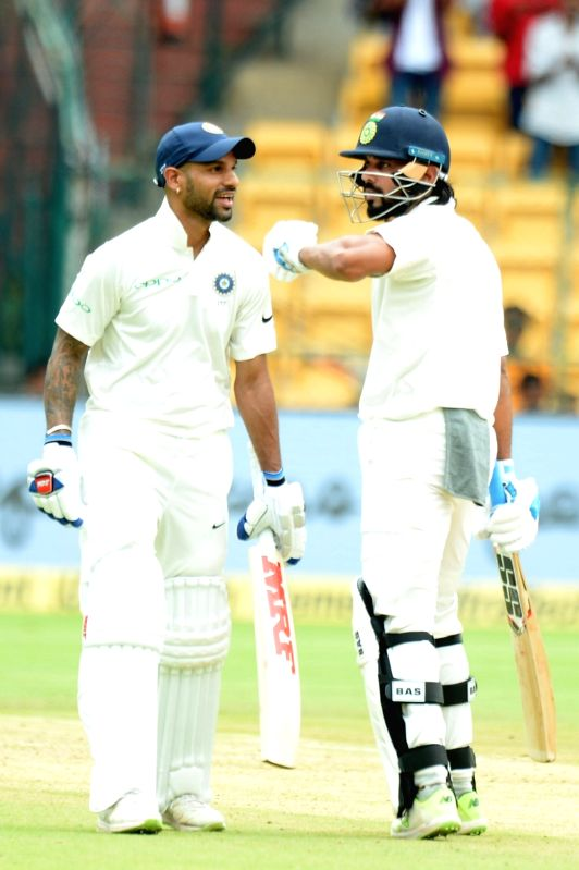 India's Shikhar Dhawan and Murali Vijay on Day 1 of the one-off test match between India and Afghanistan at M. Chinnaswamy Stadium, in Bengaluru on June 14, 2018. - Shikhar Dhawan