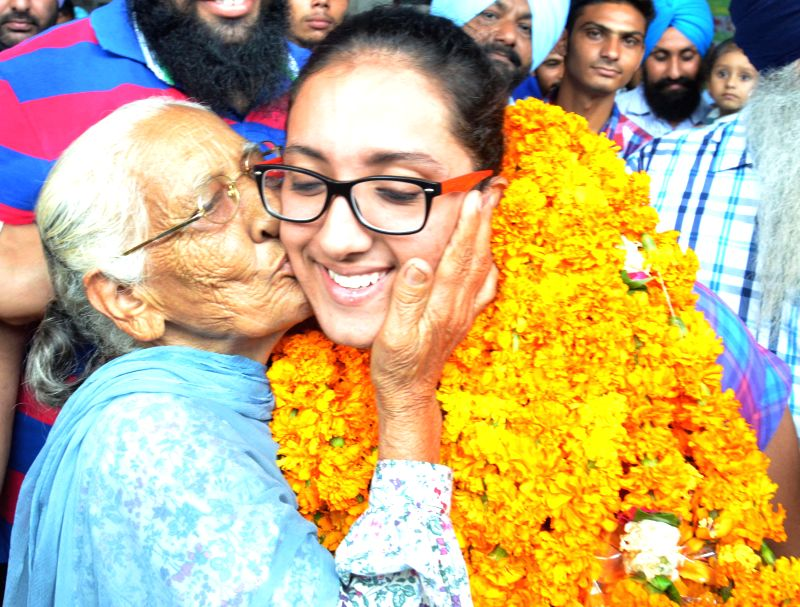 India's shining athletic star Navjeet Dhillon gets a warm welcome as she returns back with bronze medal in the women's discus throw at the 2014 IAAF World Junior Championship at Eugene, USA; in ...