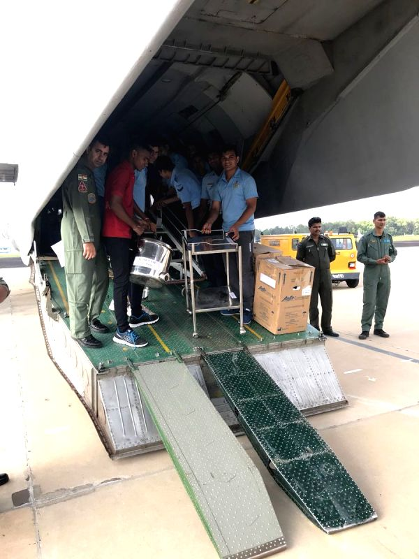Indian Air Force (IAF) personnel prepare to leave for Kerala with relief material including first aid to provide medical assistance to flood victims, from Yelahanka Airforce station, in ...