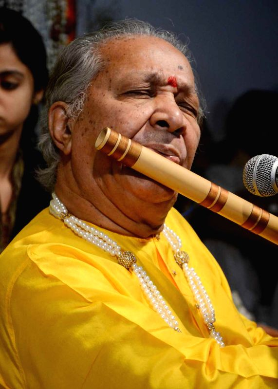 Indian classical flautist Pandit Hariprasad Chaurasia performs during a programme in Sankat Mochan Temple of Varanasi on April 20, 2014.