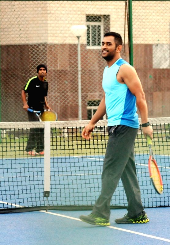Indian cricketer MS Dhoni enjoys a game of tennis during a practice session at Jharkhand State Cricket Association (JSCA) International Cricket Stadium, in Ranchi on Nov 17, 2015. - MS Dhoni