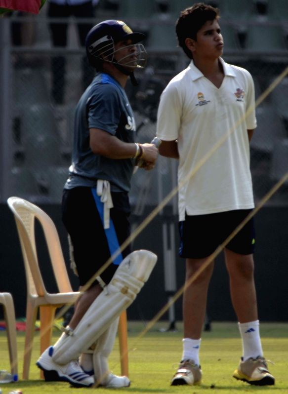 : Indian cricketer Sachin Tendulkar with his son Arjun Tendulkar during practice session ahead of his 200th and last Test match at Wankhede stadium in Mumbai on Nov.12, 2013. (Photo: Sandeep ...