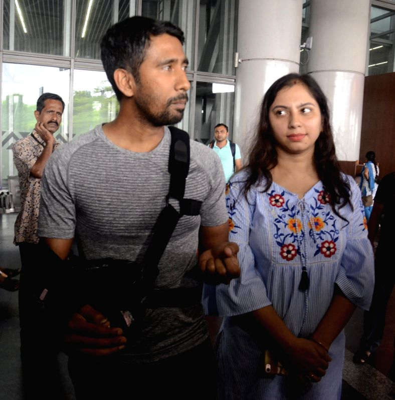 Indian cricketer Wriddhiman Saha with his wife Romi Saha at Netaji Subhas Chandra Bose International Airport, in Kolkata on Aug 9, 2018. The 33-year-old Saha underwent a shoulder surgery in ...