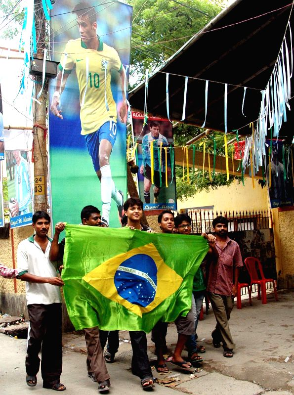 Indian fans of the Brazil football team cheer in front of Brazil football player Neymar`s poster ahead of their Round of 16 match against Chile during the FIFA World Cup 2014 in Kolkata on June 28, ..