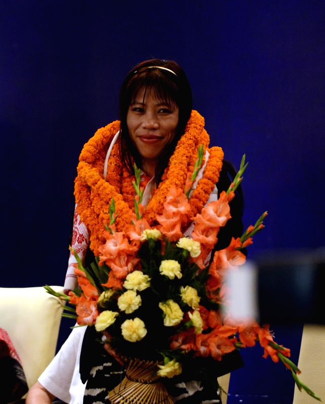 Indian female boxer Mary Kom with marigold garlands surrounds her neck gestures during a felicitation function by Union Minister of Tribal Affairs in New Delhi on August 14, 2012.Mary Kom won a bronze medal at the recently concluded Summer Olympics 2