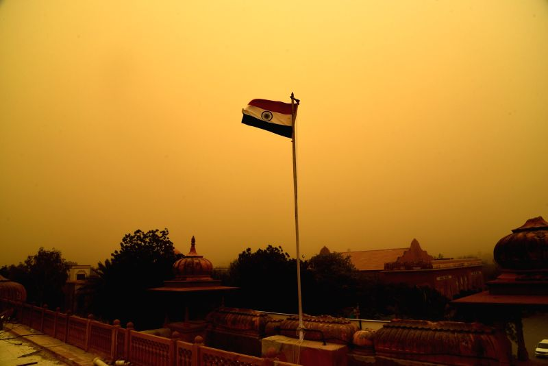 Indian flag flutters during a dust storm in Bikaner on June 14, 2018.