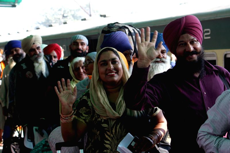 Indian Sikh pilgrims wave as they arrive at a railway station in eastern Pakistan?s Lahore, Nov. 20, 2015. Thousands of Sikh pilgrims travel to Nankana Sahib in ...